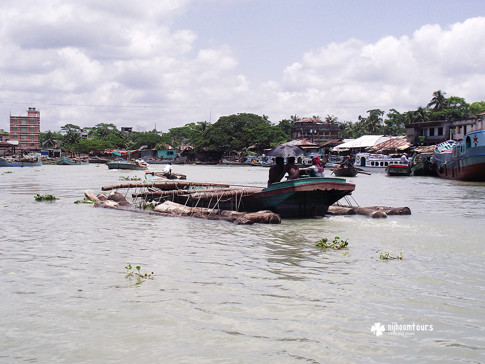 Transporting timber on boat toward the floating timber market of Barisal in Bangladesh.