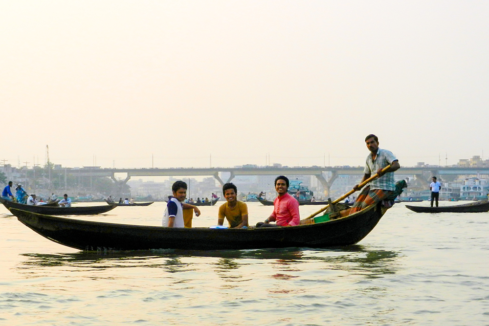 Sunset at river Buriganga on a wooden row-boat.